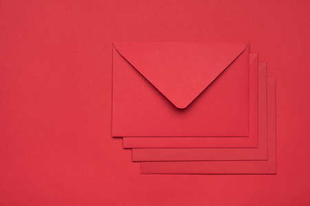 Top layout flatlay close up view photo of heap pile stack of four envelopes isolated red backdrop with empty space