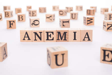 Anemia concept. Close up view photo of wooden cubes making showing word anemia on white table 写真素材