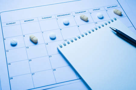 Taking pills due to time concept. Close up view photo of calendar with lying pills on the cells and open blank note pad with writing pen 写真素材