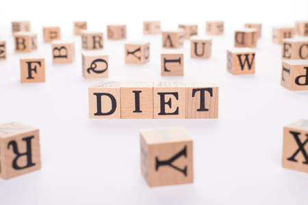 Diet concept. Close up view photo of wooden cubes making showing word diet on white table desk