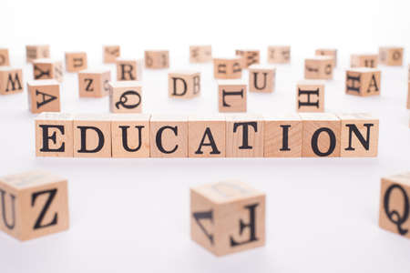 Education concept. Close up view photo of wooden cubes making showing word education isolated white desk backdrop