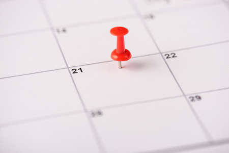 Close up view photo of red thumbtack on the 21 date on white calendar