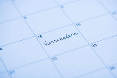 Vaccination concept. Close up view photo of word vaccination written on calendar cell