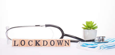 Lockdown concept. Close up panoramic view photo of medical tools face pile on masks and wooden blocks with word lockdown isolated white backdrop 写真素材