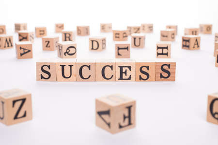Success concept. Close up view photo of wooden cubes making showing word success isolated white desk