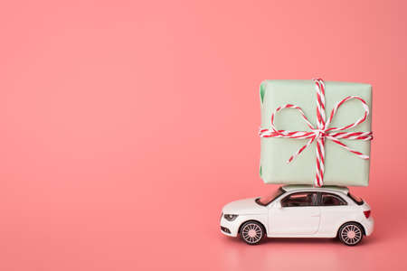 Happy 8 march concept. Side profile photo of modern car carrying large turquoise color parcel tied with rope isolated light tone backdrop with place for text