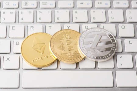 Overhead top close up view photo of silver litecoin golden ethereum and bitcoin laying on computer white keyboard background