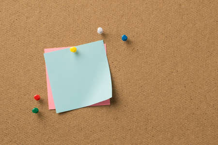 Closeup photo of clear notepaper attached to the colorful pins to the wooden backdrop
