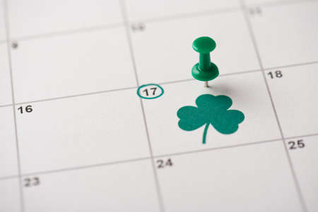 St. Patrick's day celebration concept. Cropped close up view photo of pushpin attached to paper calendar with clover image