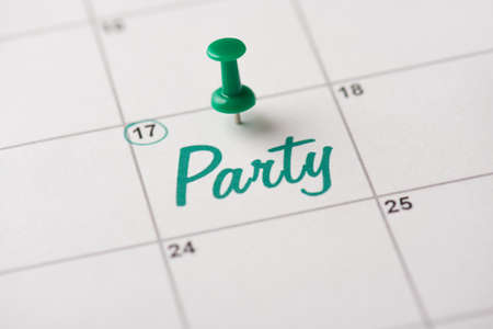 Green beer party is almost here concept. Cropped close up view photo of thumb tack attached to white calendar with word party