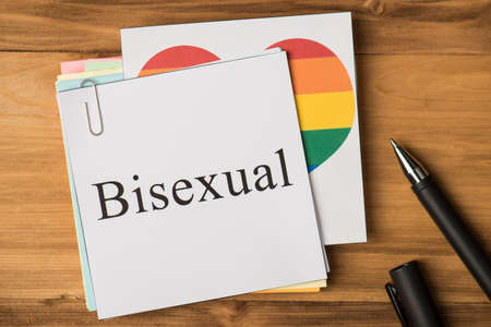 Bisexuality concept. Photo above of notes with paperclips and pen isolated on the wooden background