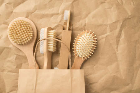 Top view photo of natural wooden bodycare and hair brushes in recycling paper bag on isolated crumpled craft paper background with copyspace