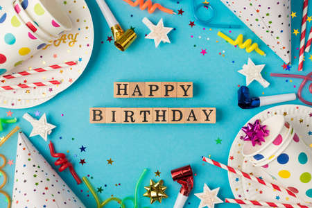Top view photo of birthday composition wooden cubes labeled happy birthday in the middle polka dots paper cups and plates sequins balloons party accessories on isolated blue table background Stockfoto