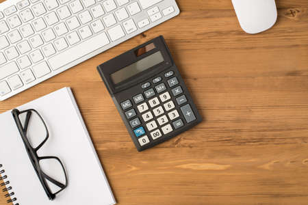 Above photo of keyboard calculator computer mouse notebook and glasses isolated on wooden backdrop