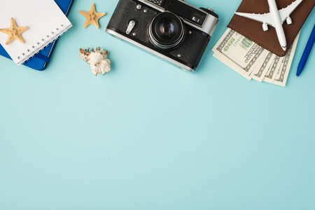Top view photo of notebooks camera pen plane model on passport cover with dollars seashell and starfishes on isolated pastel blue background with copyspace