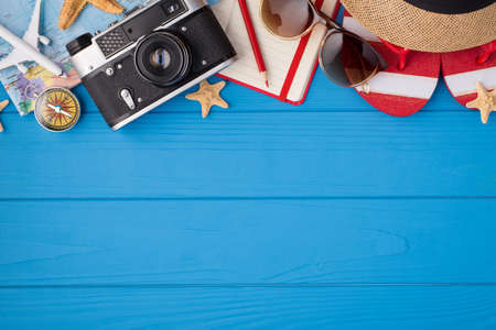 Overhead photo of camera notebook pencil compass hat sunglasses sandals map starfishes and airplane isolated on the blue background with empty space