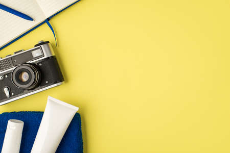 Top view photo of blue planner pen camera and two white cream bottles on towel on isolated yellow background with copyspace