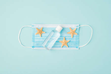 Top view photo of sanitizer bottle and starfishes on medical mask in the middle on isolated pastel blue background with copyspace