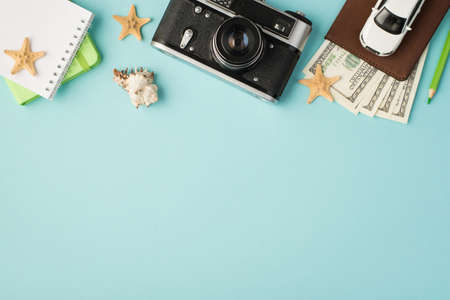 Top view photo of green copybooks camera pencil car model on passport cover with dollars seashell and starfishes on isolated pastel blue background with copyspace 免版税图像