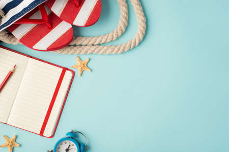 Top view photo of striped flip-flops in beach bag red copybook with pencil alarm clock and starfishes on isolated pastel blue background with copyspace