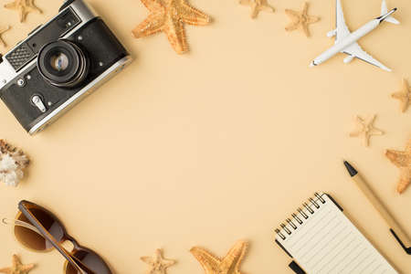 Top view photo of camera sunglasses plane model notebook pen seashell and starfishes on isolated beige background with copyspace in the middle
