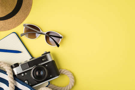 Top view photo of headwear sunglasses beach bag with blue open diary pen and camera on isolated yellow background with copyspace 免版税图像