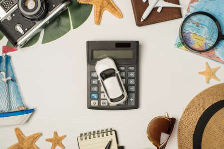 Top view photo of sunglasses hat camera map magnifier plane model on passport cover yacht toy notebook palm leaf starfishes and car model on calculator isolated wooden white background