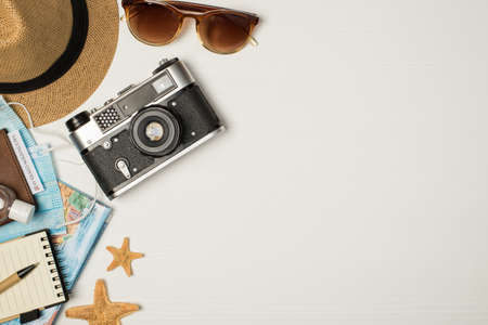 Top view photo of sunhat sunglasses camera map sanitizer on passport cover with covid test medical masks starfishes pen and notebook on isolated wooden white background with copyspace on the right 免版税图像