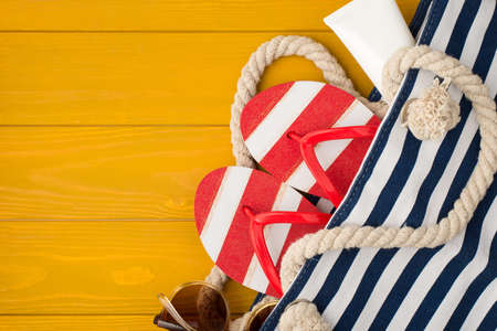 Above photo of bag with sandals sunblock and sunglasses inside isolated on the yellow wooden background with copyspace