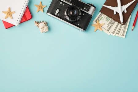 Top view photo of red notebooks camera pencil plane model on passport cover with dollars seashell and starfishes on isolated pastel blue background with copyspace
