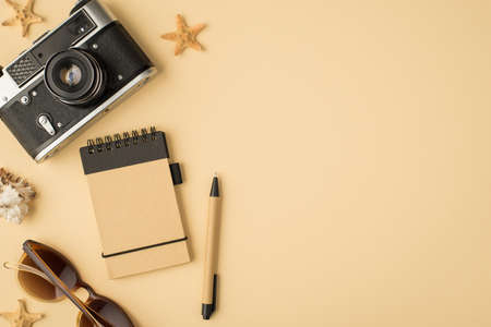 Top view photo of camera notebook pen sunglasses seashell and starfishes on isolated beige background with blank space