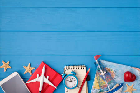 Above photo of starfishes notepad pencil map plane ship red heart alarm clock and phone isolated on the blue wooden background with empty space