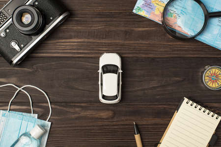 Top view photo of car model in the center camera map magnifier compass notebook pen medical masks and sanitizer on isolated wooden table background 免版税图像