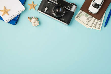 Top view photo of notebooks camera pen car model on passport cover with dollars seashell and starfishes on isolated pastel blue background with copyspace 免版税图像