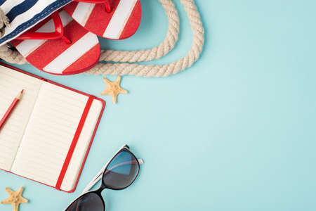 Top view photo of striped flip-flops in beach bag red planner with pencil sunglasses and starfishes on isolated pastel blue background with copyspace