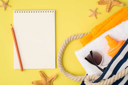 Top view photo of planner pencil starfishes beach bag with towels orange bottle sunscreen and sunglasses on isolated yellow background with blank space 免版税图像