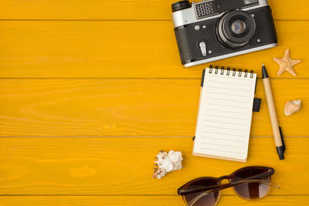 Overhead photo of camera notepad pen shell starfish and sunglasses isolated on the yellow wooden background