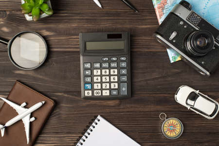 Top view photo of calculator in the center plane and car models camera map magnifier compass notebook passport cover and plant on isolated wooden table background