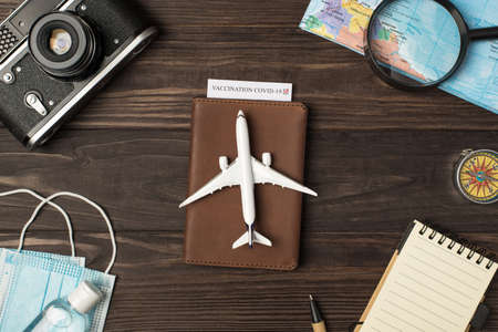 Top view photo of plane model on leather passport cover with vaccination certificate camera map magnifier compass notebook pen medical masks and sanitizer on isolated wooden table background