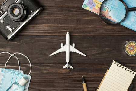 Top view photo of plane model in the center camera map magnifier compass notebook pen medical masks and sanitizer on isolated wooden table background 免版税图像