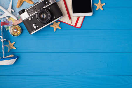 Above photo of camera starfishes notepad pencil map plane compass ship and phone isolated on the blue wooden background with empty space