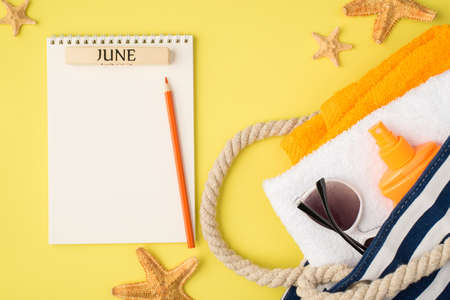 Top view photo of planner with inscription june pencil starfishes beach bag with towels orange bottle sunscreen and sunglasses on isolated yellow background with blank space