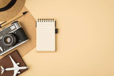 Top view photo of hat pen notebook camera plane model passport cover on craft paper envelope on isolated beige background with copyspace 免版税图像