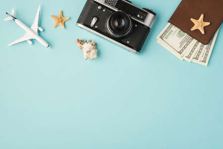 Top view photo of plane model camera seashell starfishes and passport cover with dollars on isolated pastel blue background with copyspace