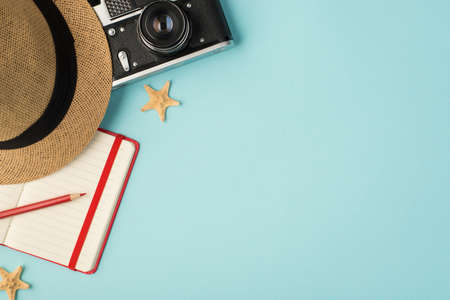 Top view photo of headwear camera red pencil planner and starfishes on isolated pastel blue background with copyspace 免版税图像