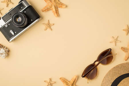 Top view photo of camera hat glasses seashell and starfishes on isolated beige background with copyspace 免版税图像