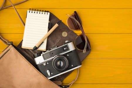 Overhead photo of camera notepad pen sunglasses and bag isolated on the yellow wooden background