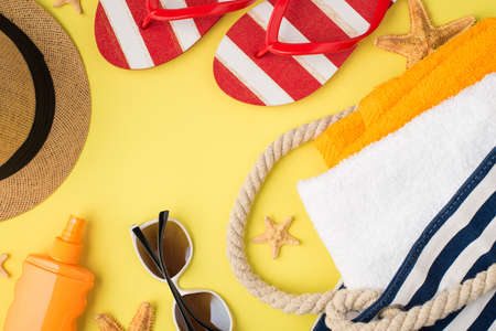 Top view photo of starfishes beach bag with orange and white towels sunscreen bottle hat sunglasses and flip-flops on isolated yellow background 免版税图像