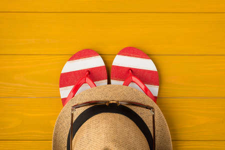 Above photo of sandals sunglasses and sunhat isolated on the yellow wooden background