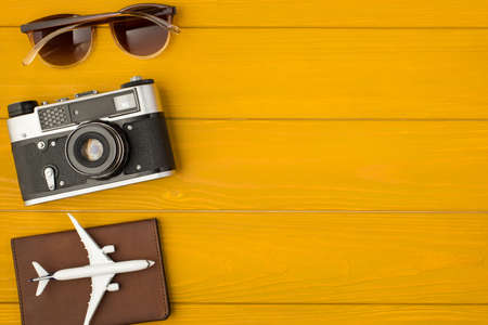 Above photo of camera passport airplane and sunglasses isolated on the wooden background with copyspace